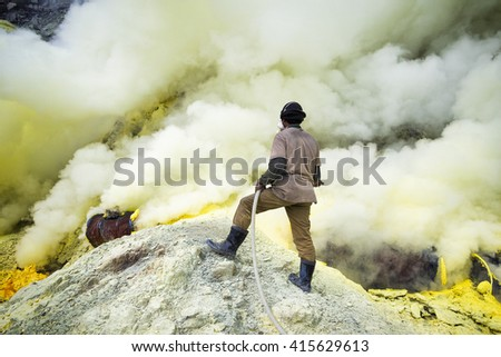 Kawah Ijen Volcano, East Java, Indonesia - May 25: Sulfur miner spraying water onto pipes inside the crater of Kawah Ijen volcano in East Java, Indonesia.