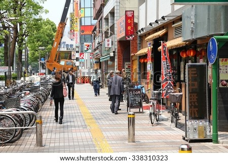 KAWASAKI, JAPAN - MAY 10, 2012: People walk in Kawasaki, Japan. Kawasaki city is inhabited by 1.44 million people.