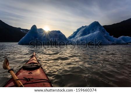 Kayak approaches as Alaskan summer setting sun creates star-burst on crest of iceberg - stock photo