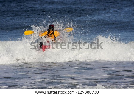 Kayak-er on the crest of a wave in rough sea of Nova Scotia coast, Canada - stock photo