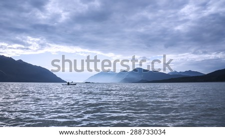 Kayak in rough water with storm clouds in the Chilkat Inlet near Haines Alaska in evening light.