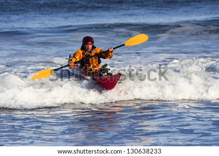 Kayak man over big wave on rough sea of Nova Scotia coast, Canada
