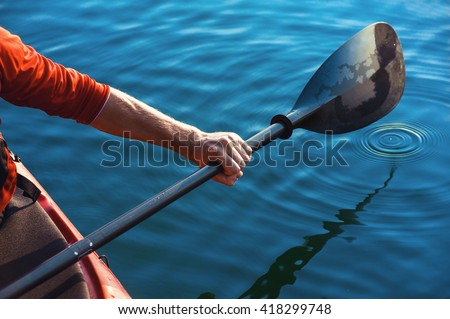 kayak man's hand holding a red paddle