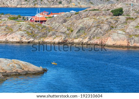 Kayak paddlers on the sea at rocky coast - stock photo