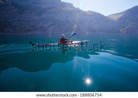 Kayak. People kayaking in the sea. Leisure activities on the calm blue water. - stock photo