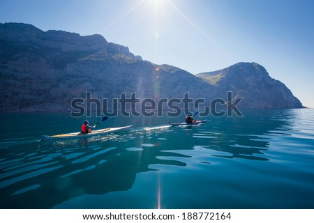 Kayak. People kayaking in the sea near the mountains. Activities on the water. - stock photo