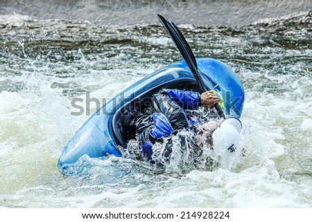 Kayak rolling on whitewater. Focus on back of kayak and water  - stock photo