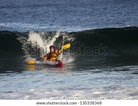 Kayak surfer escaping from big wave on rough sea in Black Cove, Nova Scotia coast, Canada - stock photo