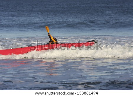 Kayak surfer hitting a rough wave by the side  on  sea of Nova Scotia coast, Canada - stock photo