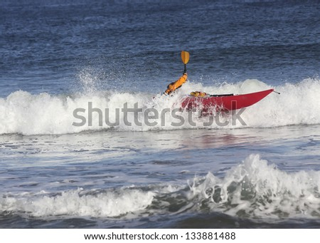 Kayak surfer hitting a rough wave  on the crest of a wave in rough sea of Nova Scotia coast, Canada  on the crest of a wave in rough sea of Nova Scotia coast, Canada - stock photo