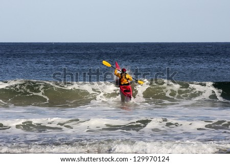 Kayak surfer over the crest of a wave in rough sea of Nova-Scotia coast, Canada - stock photo