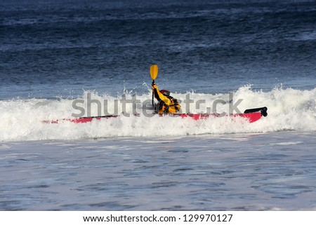 Kayak surfer over the crest of a wave in rough sea of Nova-Scotia coast, Canada