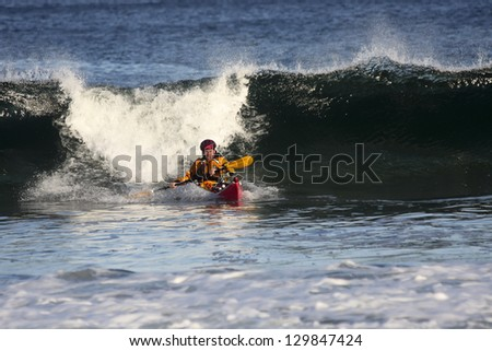 Kayaker escaping from big wave on rough sea in Black Cove, Nova Scotia coast, Canada - stock photo