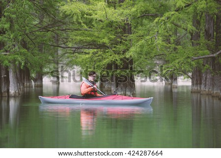 Kayaker floating into flooded forest. Toned Image. - stock photo
