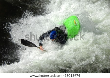 Kayaker goes under the boiling water on a raging river in North Carolina.  His kayak is green and his helmet is blue. - stock photo