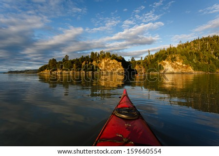 Kayaker heads toward land in remote Alaskan wilderness on sunny afternoon in summer