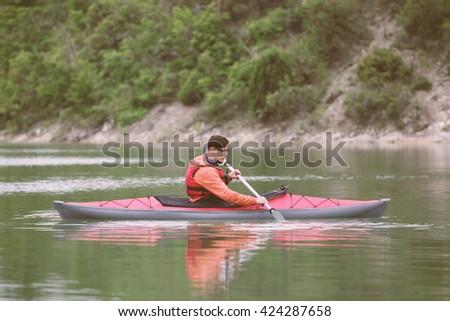 Kayaker paddling on the lake. Toned Image. - stock photo