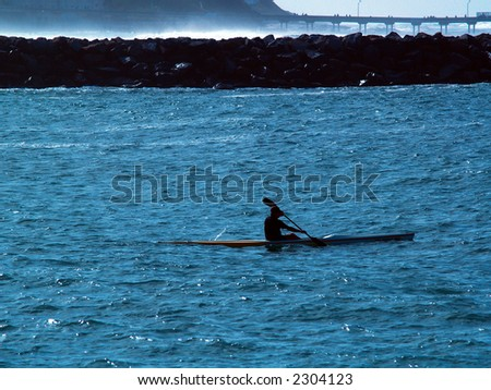 Kayaker rowing in the ocean.