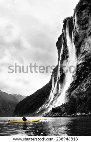 Kayaker takes a foto of Waterfall Seven Sisters at rainy day. Yellow kayak on a monochromatic background - stock photo