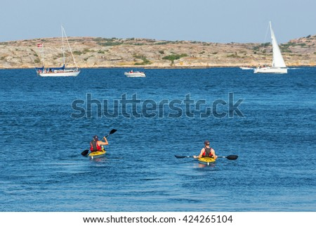 Kayakers in the sea at rocky archipelago in summer - stock photo