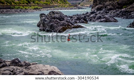 Kayakers navigating through the White Waters of the Fraser River as the river winds its way through the Fraser Canyon - stock photo