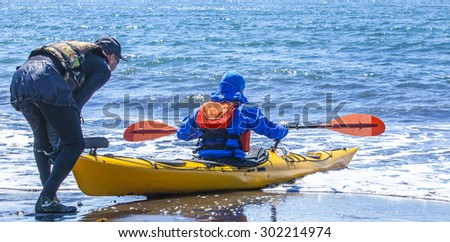 Kayakers on sand coast of Pacific ocean on Kamchatka