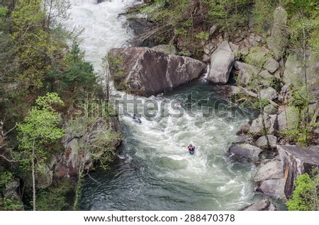Kayakers paddle over rapids below Toccoa Falls - stock photo