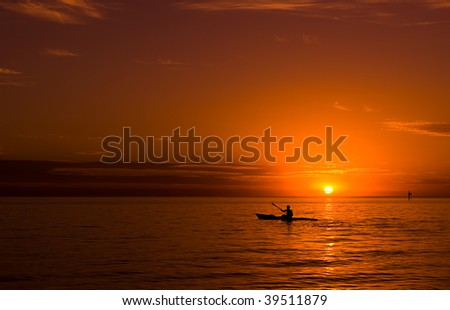 Kayaking at sunset in the ocean. - stock photo
