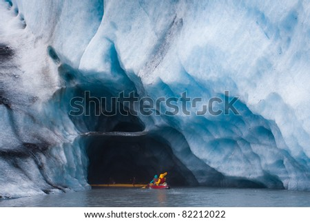 Kayaking into blue ice cave in glacier iceberg, Alaska