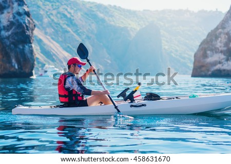 Kayaking. Man fisherman floats on a white kayak for fishing along the coast of the island near the rocks. Canoeing adventure on a calm sea with blue water.