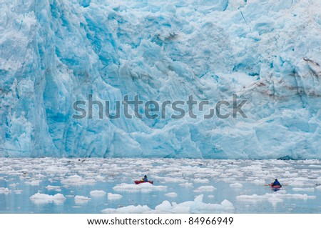 Kayaking near the foot of majestic Surprise Glacier. - stock photo