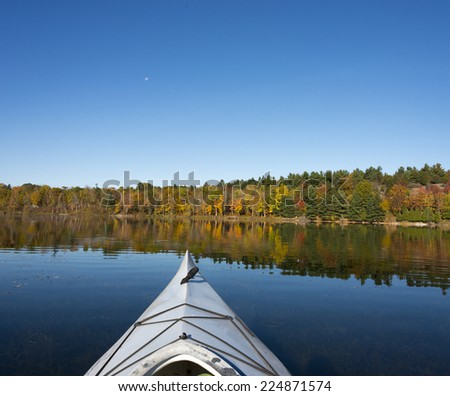 Kayaking on a northern lake in autumn with intense blue sky and vibrant fall colors - stock photo