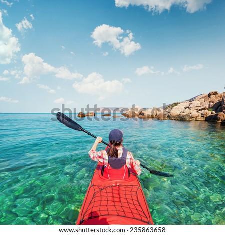 Kayaking. The woman floating on the sea kayak. Leisure activities on the sea. Canoeing. - stock photo