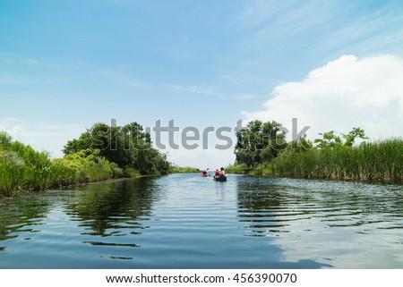 Kayaking through lush green Bayou surrounded by swamp lands in Louisiana, USA - stock photo