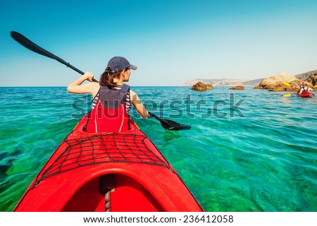 Kayaking. Woman floating on the sea kayak. Leisure activities on the sea. Canoeing. - stock photo