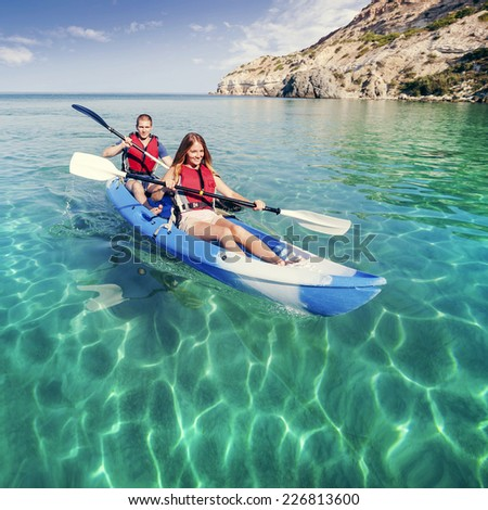 Kayaking. Young couple is sailing on a sea kayak. Sports and recreation on the water. - stock photo