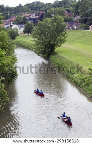 Kayaks and canoes floating down a river - stock photo