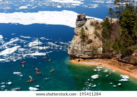 Kayaks maneuver through ice floes to view Miners Castle on Lake Superior. Late ice breakup created unusual ice formations at Pictured Rocks National Lakeshore in the Upper Peninsula of Michigan - stock photo