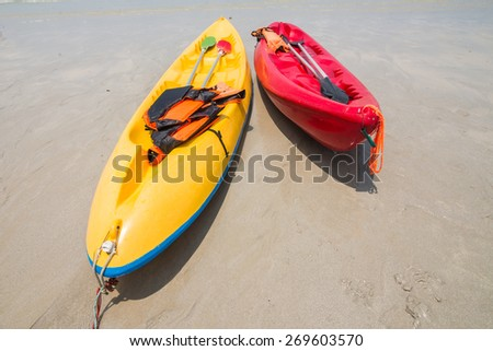 Kayaks on a beautiful beach and blue sky - stock photo