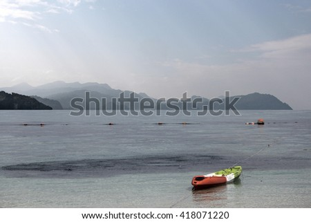 kayaks on the beach by the sea on a background of mountains - stock photo