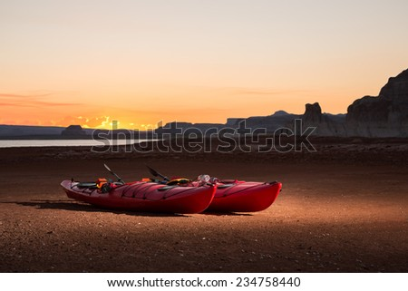 Kayaks Sit on the Receding Shoreline of Lake Powell. - stock photo