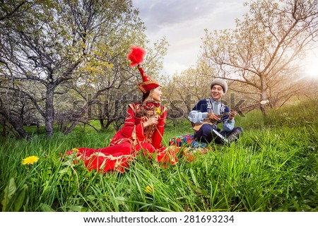 Kazakh man playing dombra and singing the song for woman in red on the green grass in Almaty, Kazakhstan, Central Asia - stock photo
