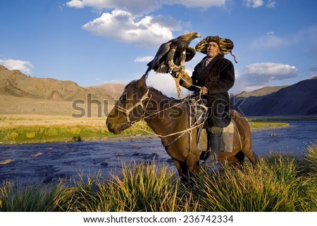 Kazakh men traditionally hunt foxes and wolves using trained golden eagles  - stock photo