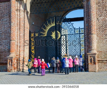 Kazan, Tatarstan, Russia -  February 20, 2016:  Historic Complex of the Kazan Kremlin. UNESCO World Heritage Site. The teacher-guide and group of schoolchildren near iron gate of the tower Syuyumbike.