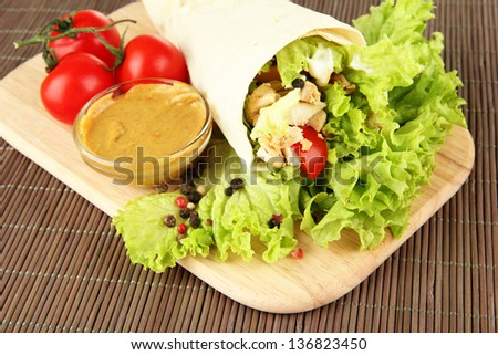 Kebab - grilled meat and vegetables, on wooden board, on bamboo mat background