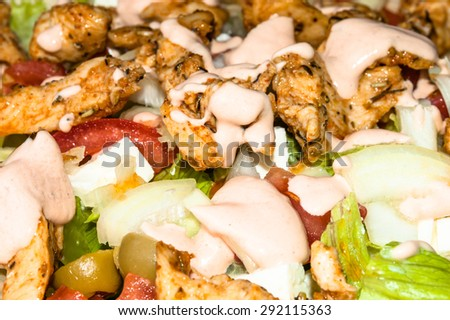 Kebab gyros salad with grilled meat and vegetables topped with sauce, macro close-up, food background