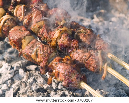 Kebabs cooking on the grill with smoke - stock photo
