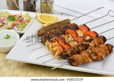 Kebabs - Selection of chicken tikka, paneer tikka and seekh kebabs served with crunchy salad, mint raita and lemon wedges. - stock photo