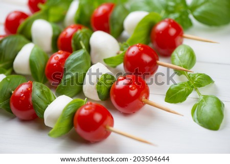 Kebabs with tomatoes, cheese and basil over white wooden surface - stock photo