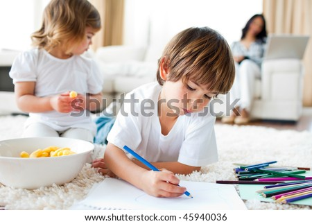 Keen little boy drawing lying on the floor in the living-room
